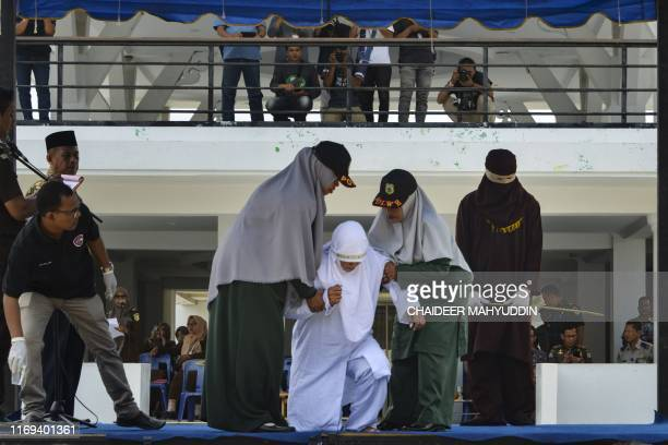 A woman is assisted by members of the Sharia police after being whipped in public in Banda Aceh on September 19 2019 A trio of canoodling couples...