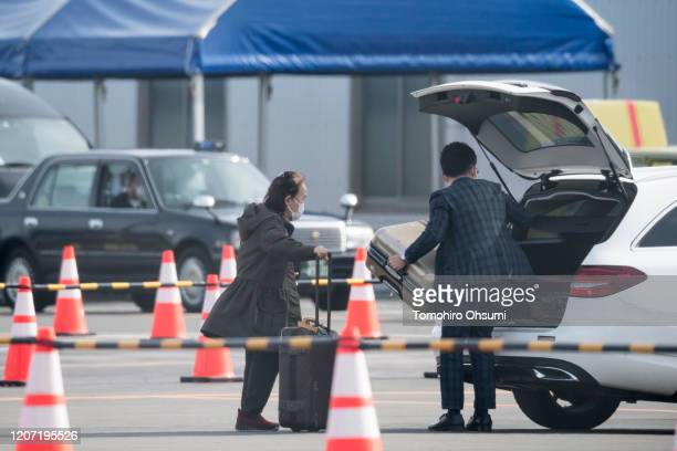 A woman is assisted while loading baggage on a vehicle after disembarking the quarantined Diamond Princess cruise ship at Daikoku Pier on February 19...