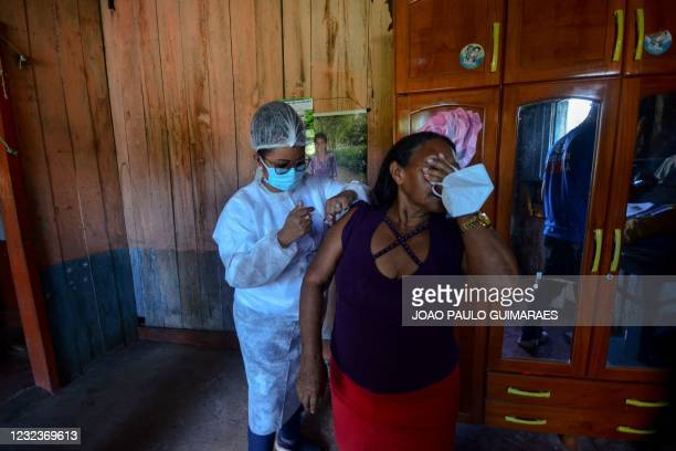 Woman is being inoculated with the Oxford-AstraZeneca vaccine against the novel coronavirus disease, COVID-19, in Moju, Para State, Brazil, on April...