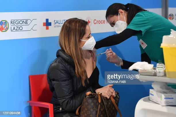 Woman is being vaccinated on February 11, 2021 at a hub for Covid-19 vaccinations located in Rome's Fiumicino airport long-term parking area. - The...