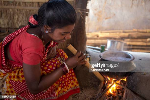 A woman is blowing into a fire with a wooden tube in a rural area about 300 Kilometer from Kolkata