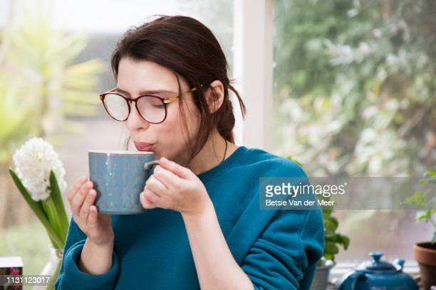 woman is blowing into hot drink, eye glasses are steamed up. - 蒸し ストックフォトと画像