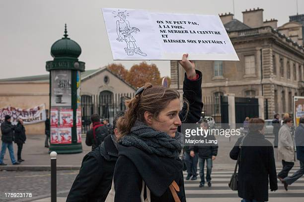 CONTENT] A woman is branding a placard against austerity among the crowd during Europe's day of antiausterity strikes and protests in Paris on...