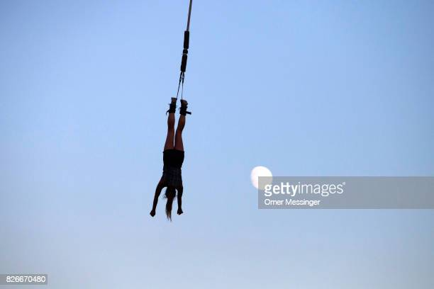 A woman is bungee jumping as the moon is seen in the background at the 2017 Woodstock Festival Poland on August 4 2017 in Kostrzyn Poland The...