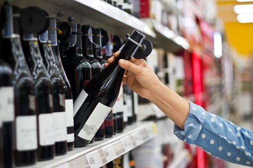 Woman is buying a bottle of wine at the supermarket background 905866588