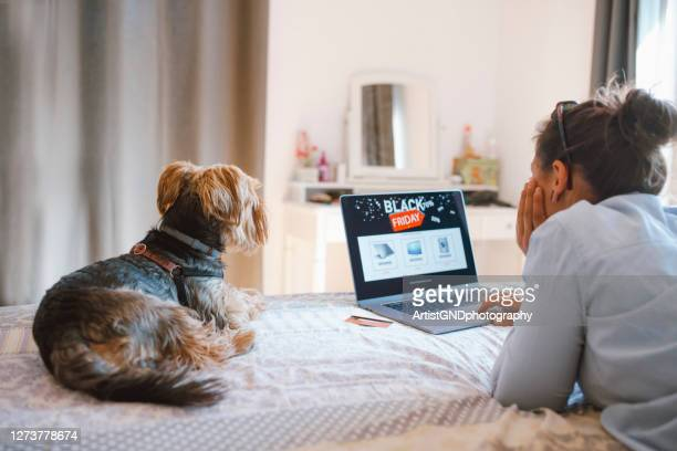 woman is buying electronics online at black friday discounts - black friday stock pictures, royalty-free photos & images