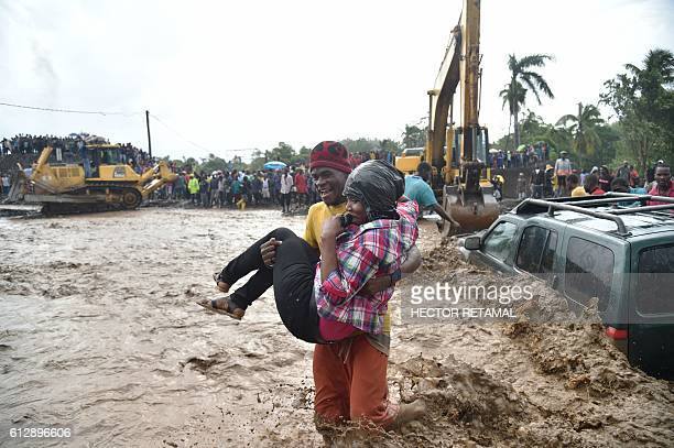 A woman is carried across the river La Digue in Petit Goave where the bridge collapsed during the rains of the Hurricane Matthew southwest of...