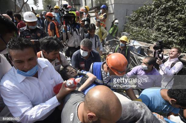 A woman is carried away after being pulled out of the rubble following a quake in Mexico City on September 19 2017 A powerful earthquake shook Mexico...