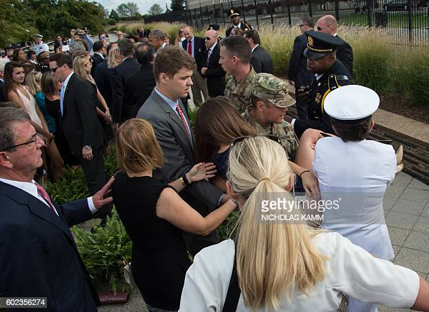 A woman is carried away after fainting during a ceremony commemorating the September 11 2001 attacks at the Pentagon in Washington DC on September 11...