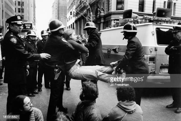 A woman is carried away by police officers wearing riot gear during an antinuclear demonstration in Lower Manhattan New York City 1979