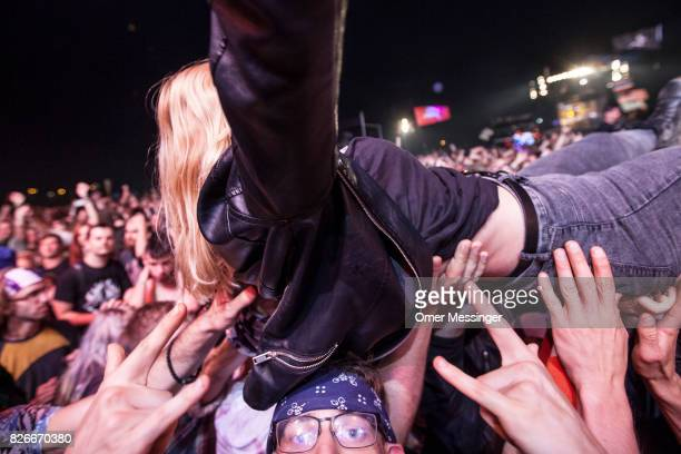 A woman is carried by the crowd as a man under her gestures to the camera at the 2017 Woodstock Festival Poland on August 4 2017 in Kostrzyn Poland...