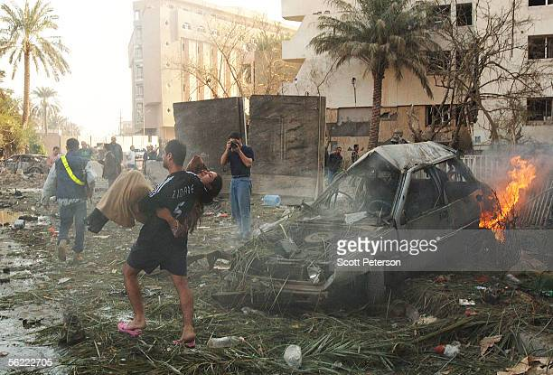 Woman is carried to safety past a burning car in the aftermath of a double suicide car bomb attack that struck civilians living near the blast walls...