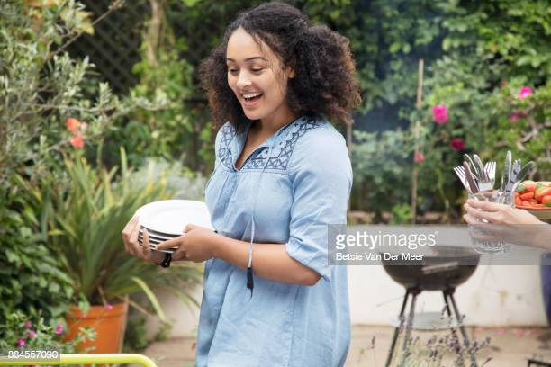 Woman is carrying plates for setting table, in preparation for garden party.