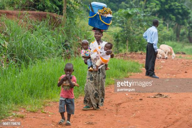 woman is carrying tow babies in rural congo - congo stock pictures, royalty-free photos & images