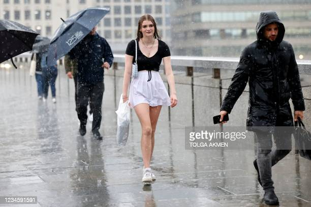 Woman is caught out by a heavy rain shower as she crosses London Bridge in central London on August 9, 2021.