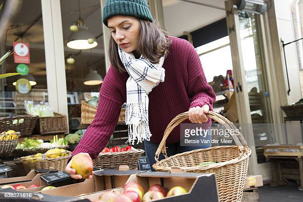 Woman is choosing apples, holding shopping basket at organic food shop.