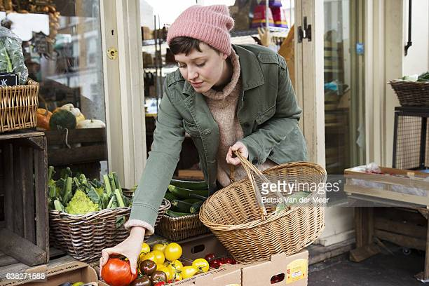 Woman is choosing organic tomatoes and is placing them in her basket at organic farm shop.