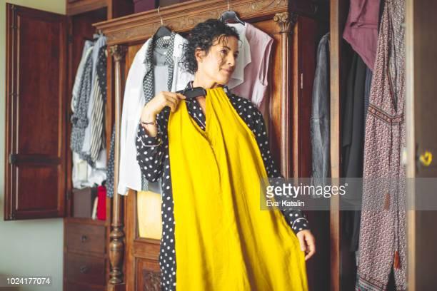 frau ist die wahl der richtigen kleidung zu tragen - anprobieren stock-fotos und bilder