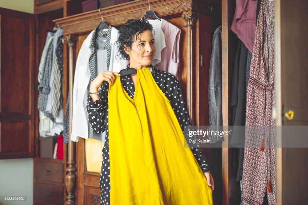 Mulher é escolher o vestido certo para vestir : Foto de stock