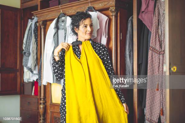 woman is choosing the right dress to wear - clothing stock pictures, royalty-free photos & images