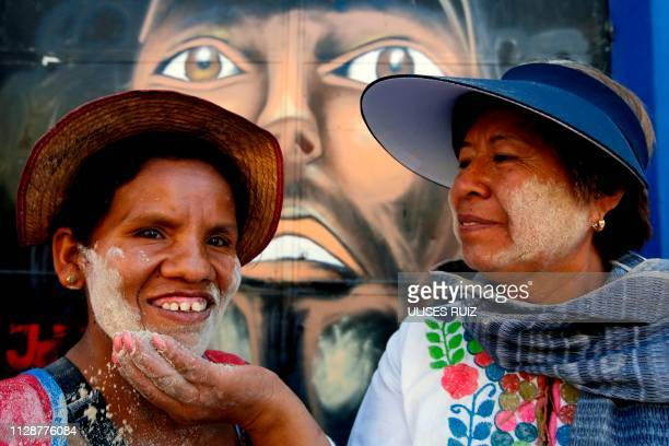 A woman is coated with pinol by a Pinolera during carnival celebrations in San Martin de las Flores Tlaquepaque Mexico on March 5 2019 The tradition...