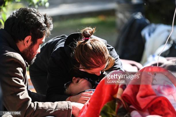 Woman is comforted after officials comfirmed that both her parents were dead during the ongoing search operation at the site of a collapsed building...