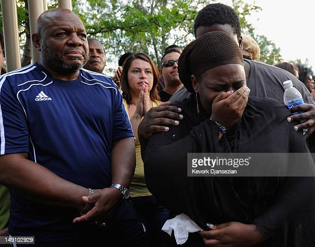 A woman is comforted when she is overcome with grief during a prayer vigil for the victims of Friday's movie theater mass shooting at the Aurora...