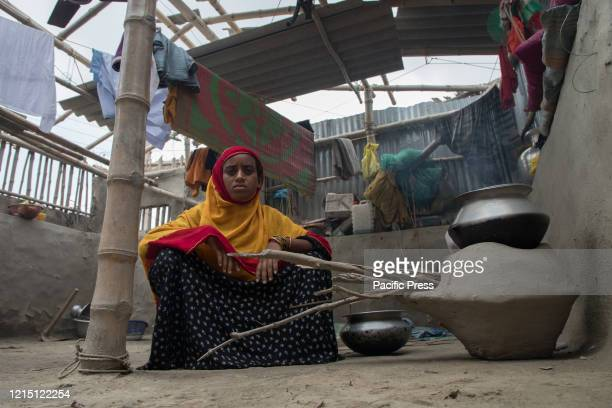 A woman is cooking rice under the broken roof of her own house after the super cyclone Amphan hit her village which is situated in the coastal area