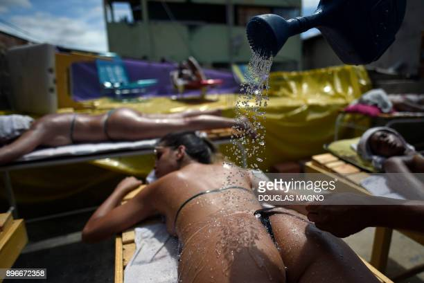 A woman is cooled down with a watering can as she sunbathes using insulating tape at a beauty center in Belo Horizonte Brazil on December 21 2017...