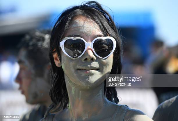 A woman is covered with mud on her face during the 21th Boryeong Mud Festival at Daecheon beach in Boryeong on July 14 2018 The annual festival which...