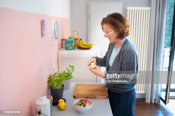 A woman is cutting an apple in her kitchen on April 08 2020 in Bonn Germany
