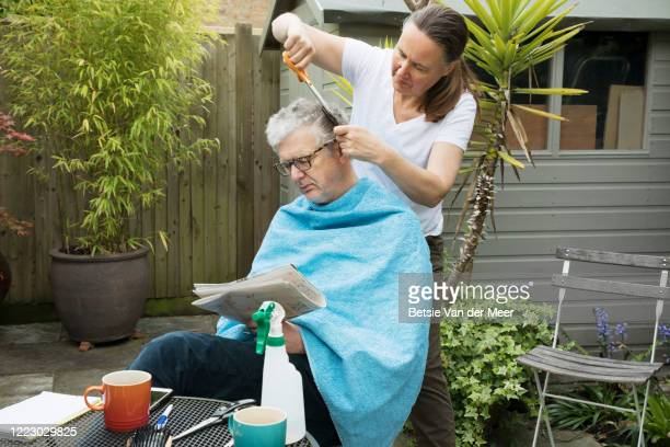 woman is cutting mature man's hair in back garden, during lockdown. - makeshift stock pictures, royalty-free photos & images