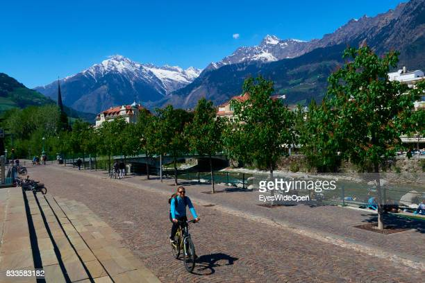 A woman is cycling through the green city centre of Meran in South Tyrol on April 21 2015 in Lana Italy