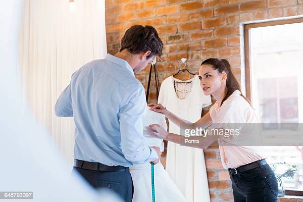Woman is discussing with designer over dress
