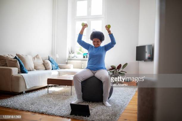 woman is doing online workout during covid-19 lockdown - abstand halten infektionsvermeidung stock-fotos und bilder