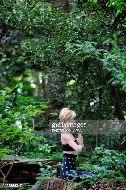 a woman is doing yoga in the forest. - 生い茂る ストックフォトと画像