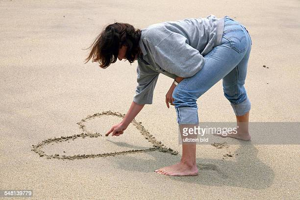 woman is drawing a heart into the sand at the beach