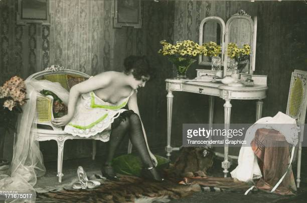 A woman is dressing at her vanity in this postcard issued circa 1910 in Germany