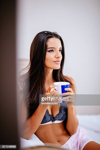 Woman is drinking coffee in bed while thinking about something