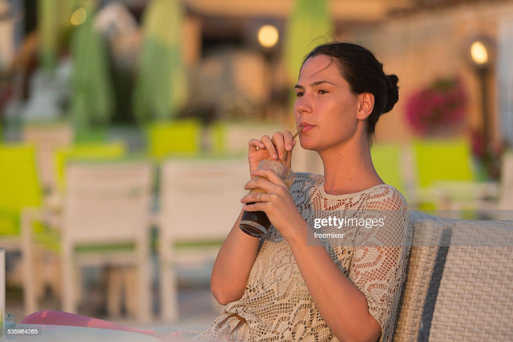 Woman is drinking juice and enjoy the beautiful seascape : Stock Photo