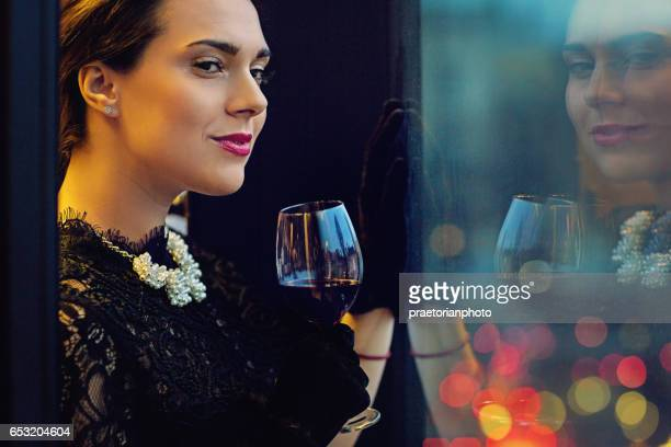 Woman is drinking wine and looking trough the window