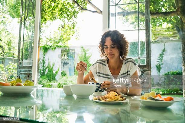 Woman is eating breakfast while sitting at table