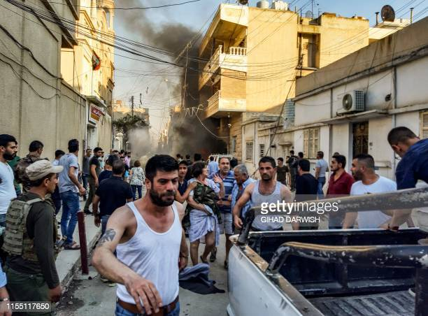 Woman is escorted away from the scene of a car bomb explosion outside the Syriac Orthodox Church of the Virgin Mary in the predominantly Christian...