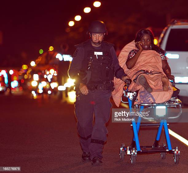 120716 TORONTO ONTARIO A woman is escorted by an EFT officer to a waiting ambulance Several people including one reported dead were shot in the...