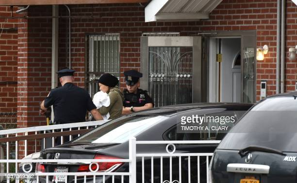 A woman is escorted by NYPD from the Mei Xin Care Incorporated day care center located at the owners home in the Flushing area of Queens on September...