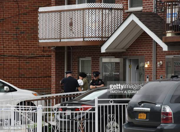 A woman is escorted by NYPD out of a daycare center Mei Xin Care Incorporated located at the owners home in the Flushing area of Queens September 21...