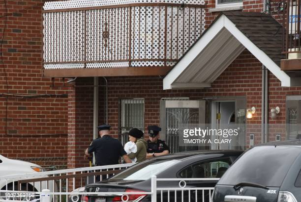 A woman is escorted by NYPD out of a daycare center the Mei Xin Care Incorporated located at the owners home in the Flushing area of Queens September...