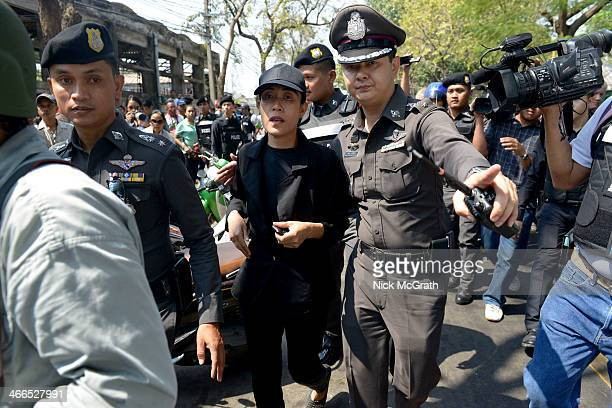 A woman is escorted by police from Din Daeng polling station after government supporters harassed her for wearing an antigovernment whistle around...