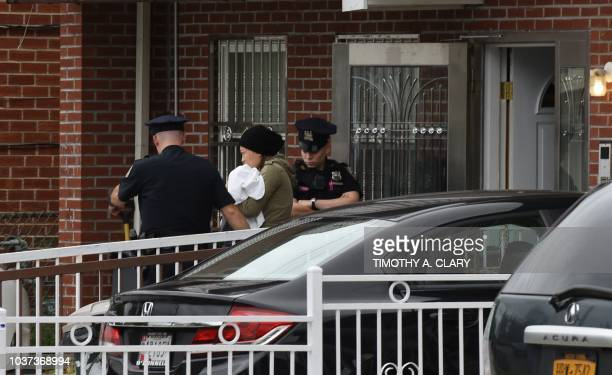 A woman is escorted by police out of a daycare center Mei Xin Care Incorporated located at the owners home in the Flushing area of Queens September...