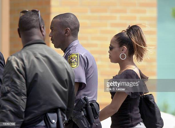 A woman is escorted into the public funeral for singer Lisa Left Eye Lopes at the New Birth Missionary Baptist Church May 2 2002 in Lithonia GA Lopes...